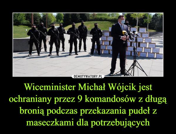 Wiceminister Michał Wójcik jest ochraniany przez 9 komandosów z długą bronią podczas przekazania pudeł z maseczkami dla potrzebujących –
